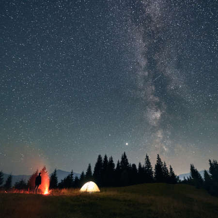 Back view of male traveler standing near campfire and camp tent under night sky with stars. Magnificent view of blue starry sky under grassy hill. Concept of travelling, hiking and night camping.