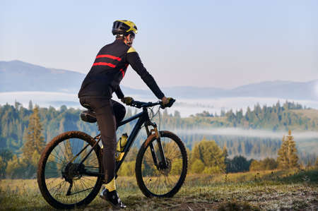 Back view of male cyclist in cycling suit standing with bike with coniferous trees and hills on background. Man bicyclist enjoying bicycle ride in mountains. Concept of sport, biking, active leisure.
