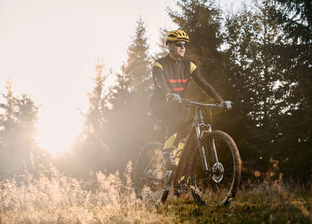 Male cyclist riding mountain bicycle on sunny day.