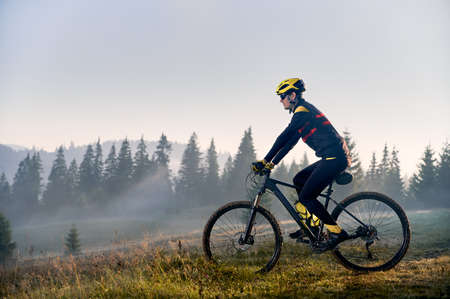 Young man riding bicycle in the mountains in early morning Standard-Bild