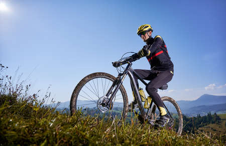 Joyful male cyclist riding bicycle uphill under blue sky.