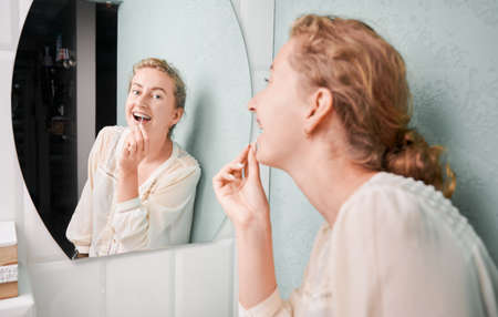 Cheerful young woman brushing teeth with braces.