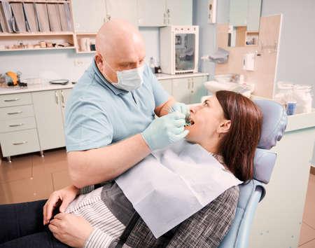 Doctor examining female patient teeth in dental office.