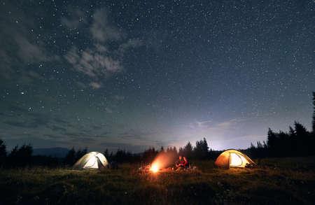 Hikers standing near campfire under beautiful starry sky. Standard-Bild