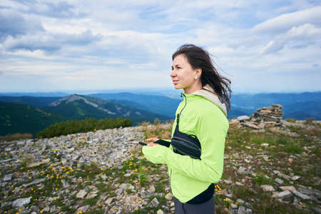 Woman is holding smartphone, mountains on background.