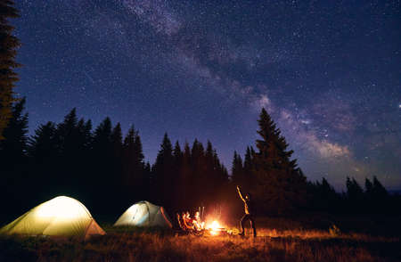 Man is showing his friends Milky Way over tent city. Outdoor recreation