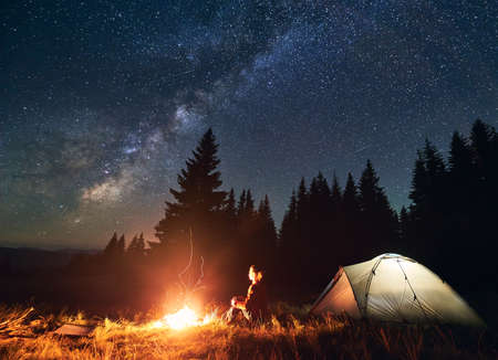 Girl is sitting by the fire on background of tent and spruce forest under starry sky on which milky way is visible