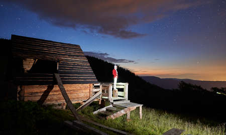 Horizontal snapshot of young woman in the mountains watching beautiful starry night from a wooden hut porch. Picturesque sunset in summer mountains. Copy space. Concept of astrophotography Zdjęcie Seryjne