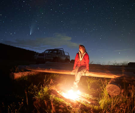 Young woman sitting on bench near cozy bonfire and looking at starry sky. Comet Neowise and car on background. Concept of enjoying incredible nature and fresh air at night.