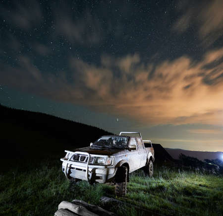Dirty big car in the mountains at night. Concept of travelling, resting on nature and looking at starry sky with car.