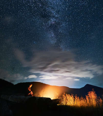 Tourist resting near bonfire and nature in the evening. Man enjoying fresh air and starry sky at night. Concept of travelling, hiking, night camping and astronomy.