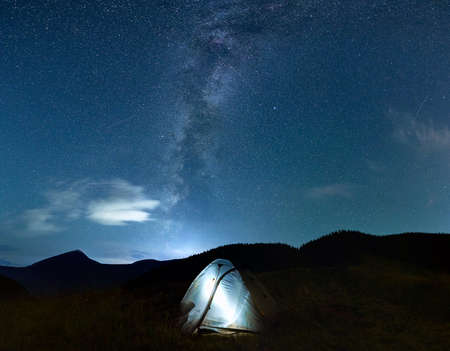 Panoramic view of night starry sky over grassy hill with illuminated tourist tent. Scenery of mountain valley with camp tent under blue sky with stars and Milky Way. Concept of night camping. Zdjęcie Seryjne