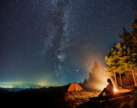 Silhouette of young woman sitting and resting near tent and campfire in the mountains. Concept of relaxation under starry sky with Milky way. Standard-Bild