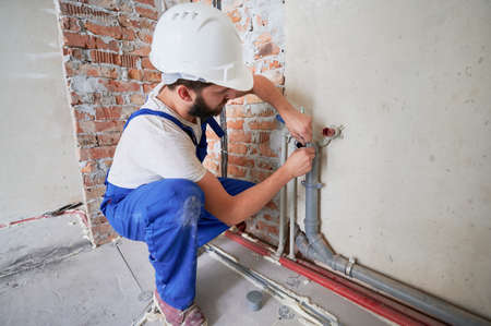 Man in safety helmet lubricating water pipe to reduce friction and provide long-lasting lubrication. Male plumber in work overalls installing water system in apartment. Plumbing works concept.