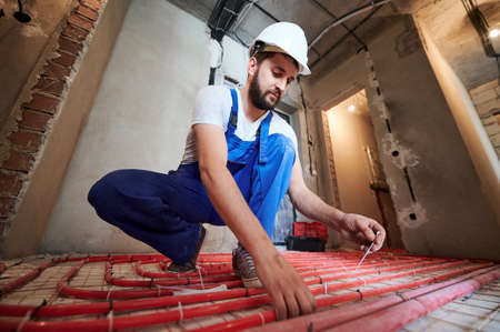 Horizontal, low angle view portrait of young plumber wearing blue overalls and white helmet, tying up red tubes on the floor heating system in new unfinished apartment Stok Fotoğraf
