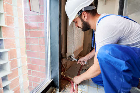 Side view of bearded young man in work overalls installing heating radiator in room. Male worker in safety helmet using wrench in apartment. Concept of radiator installation and plumbing works.