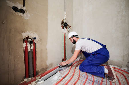 Wide angle view on young worker standing on his knees in blue overalls and helmet installing underfloor heating system and plumbing system. Empty room with many pipes. Construction concept