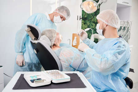 Horizontal snapshot in dentist office of dentist and his assistant during surgery performance. People wearing disposable closing , gloves, caps and masks. Surgical taper kit on the table.