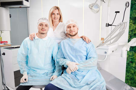 Front view of handsome male stomatologists in medical protective suits looking at camera and smiling while charming female doctor standing behind men. Concept of dentistry and dental staff.