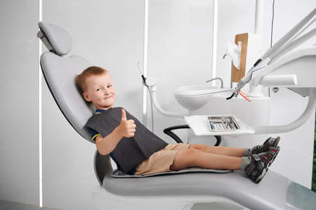 Little boy wearing black bib, sitting in dentist chair, showing thumb up. Well equipped dentist office. Concept of pediatric stomatology, dentistry and dental care. Stok Fotoğraf