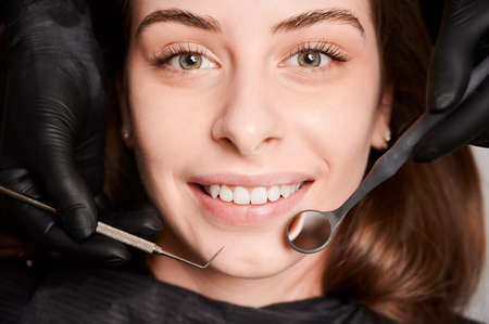 Close up portrait of beautiful young smiling woman lying in dental chair. Dentist hands in sterile gloves using dental explorer and mirror while examining female patient teeth. Concept of dentistry.