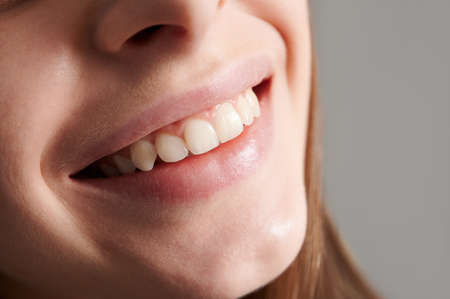 Close up of smiling female face with healthy straight white teeth. Joyful young woman demonstrating perfect toothy smile. Concept of dentistry, stomatology and dental care.
