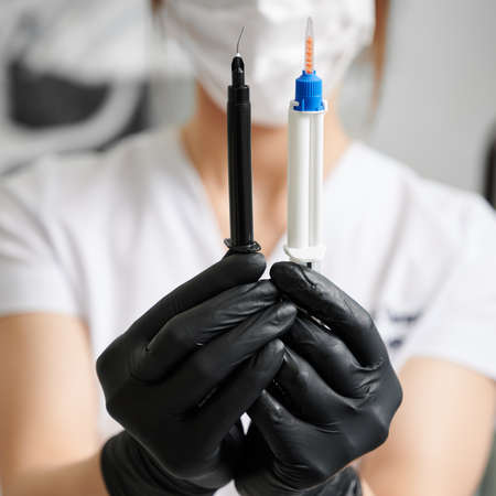 Close up of female stomatologist hands in sterile gloves holding syringe with gel for professional teeth whitening and syringe for gingival protection. Concept of dentistry and dental care.
