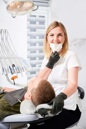 Female dentist in medical mask and sterile gloves smiling to the camera while examining male patient teeth in dental office. Vertical image. Concept of dentistry, stomatology and dental care.