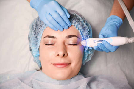 Beautician hands using aqua peel water galvanic device. Female client in disposable shower hat closing eyes and smiling while cosmetologist eliminating skin wastes in pores with special equipment.