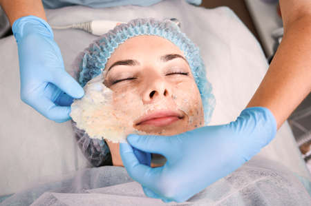 Close up of beautician hands pulling off deep cleansing mask from female client face. Woman having skincare procedure at wellness medical center. Concept of beauty, skincare and facial treatment.