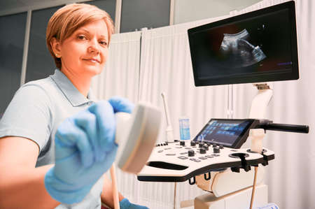 Woman physician in sterile gloves holding ultrasound transducer. Female doctor sonographer using modern ultrasound scanner in gynecological cabinet. Concept of healthcare and ultrasound diagnostics.