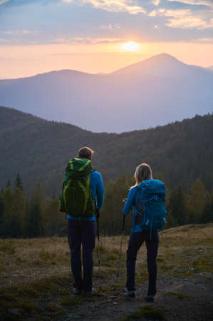 Family couple of tourists standing and enjoying view of mountain peaks and forest at dawn during hiking. Young man and woman watching for mountain landscape at dawn before active hike day.