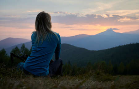 Back view of female hiker who resting after day of hike and watching at sunset above mountain beskids. Tourist enjoying landscape of mountain hills and evening sky when sun setting over horizon.
