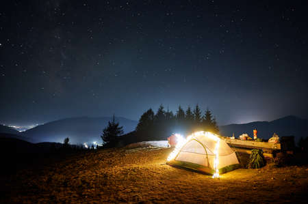 Fantastic view of night starry sky over mountains with illuminated touristic tent. Back view of hiker sitting near campfire under blue sky with stars. Concept of travelling, hiking and night camping. Stok Fotoğraf