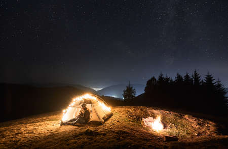 Fantastic view of starry sky over mountain valley with tourist tent and male traveler guitarist. Young man hiker sitting inside illuminated camp tent and playing guitar under night sky with stars. Stok Fotoğraf