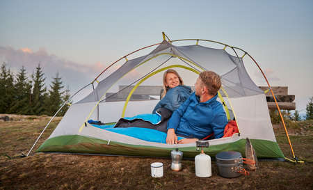 Young couple, waking up after nights sleep in tent outdoor in the mountains, happily smiling at each other, planning delicious breakfast. Pleasant morning of family pair in mountains campsite.