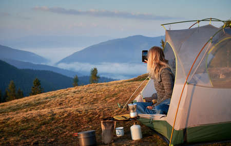 Rear view of girl photographing morning landscape with smartphone from her tent set up on hill during breakfast outdoors. Concept of active camping in the mountains, tourist equipment and photography.
