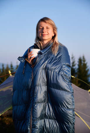 Portrait of blonde in blue sleeping bag standing near tourist tent during hike in the mountains in sunny early autumn and warming herself by hot coffee. Concept of hiking, traveling and camping. Stok Fotoğraf
