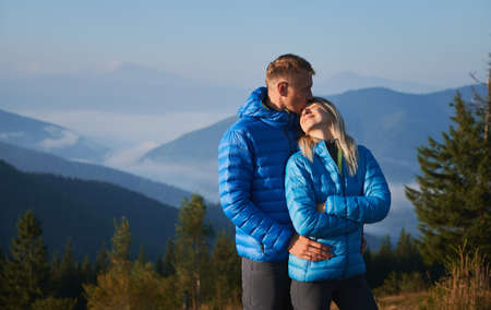 Male traveler hugging smiling woman and kissing her forehead while standing outdoors with blue sky and mountains on background. Happy couple sharing tender kiss while travelling together.