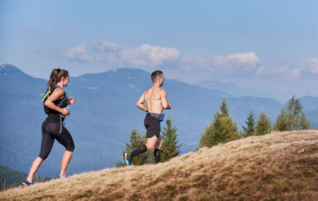 Young man and woman running up grassy hill with blue sky and mountains on background. Male and female trail runners in sportswear jogging together outdoors. Concept of sport, training and nature.