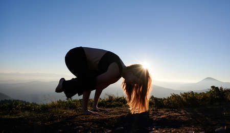 Female person in sportswear doing yoga exercise on grassy hill with blue morning sky on background. Young woman having morning workout during sunrise in mountains. Stok Fotoğraf