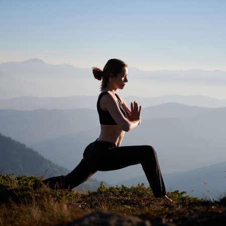 Fit young woman in sportswear doing yoga exercise outdoors in mountains. Female person doing lunge and keeping hands in prayer position while performing yoga pose on grassy hill. Stok Fotoğraf