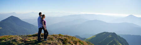 Full length of couple in love standing on grassy hill and looking at beautiful mountains. Young man traveler hugging charming woman from behind and admiring beauty of nature. Panoramic view