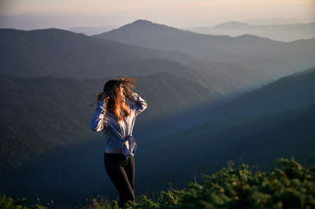 Happy female with whisk on head in mountains. Beautiful woman is posing in mountains after sunset. Concept of relaxation.
