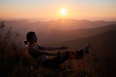 Beautiful young woman in sportswear performing yoga pose on grassy hill with yellow orange sky on background. Fit woman practicing yoga and working out in the mountains.