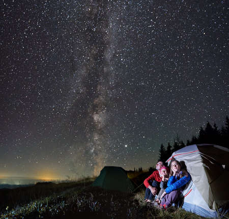 Side view of family camping in the mountains at night. Group of people in tourist tent are admiring starry sky with Milky way outdoor. Concept of campsite.