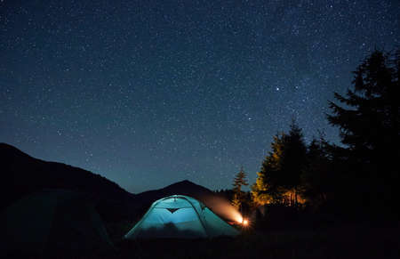 Beautiful view of night starry sky over grassy hill with tourist tents and trees. Mountain valley with illuminated camp tent under night sky with stars. Concept of hiking, night camping and astronomy.