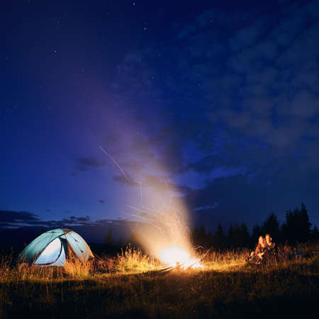 Night sky with stars and clouds over grassy hill with illuminated camp tent, campfire and hikers. Young man and woman tourists enjoying near bonfire. Concept of hiking, night camping and relationship.