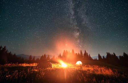 Night camping under amazing starry sky with Milky way. Wide angle view on beautiful landscape in the mountains. Two tents and campfire, wall of spruces on background. Concept of astrophotography.