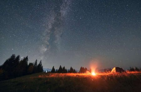 Night camping under amazing starry sky with Milky way. Beautiful landscape in the mountains. Two tents and campfire, wall of spruces on background. Concept of travelling and astrophotography